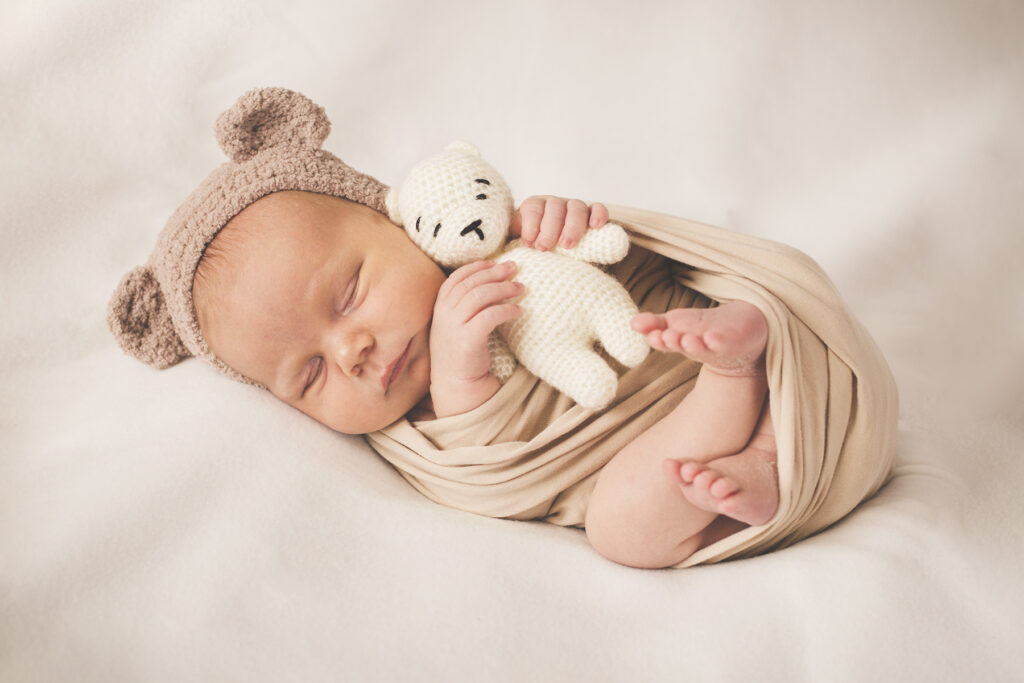 Newborn Baby in Neutral Outfit with Bear Hat and Stuffed Bear