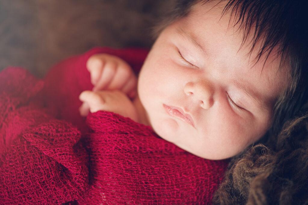 Newborn Baby in Red Gauze Wrap